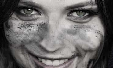 close up woman s face hands covered mud young woman dirty face arms dark background close up 115997228